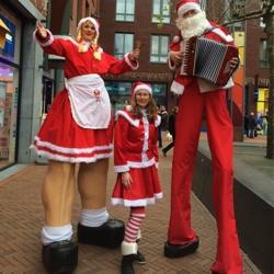 kerstmeisje en kerstman op stelten boeken